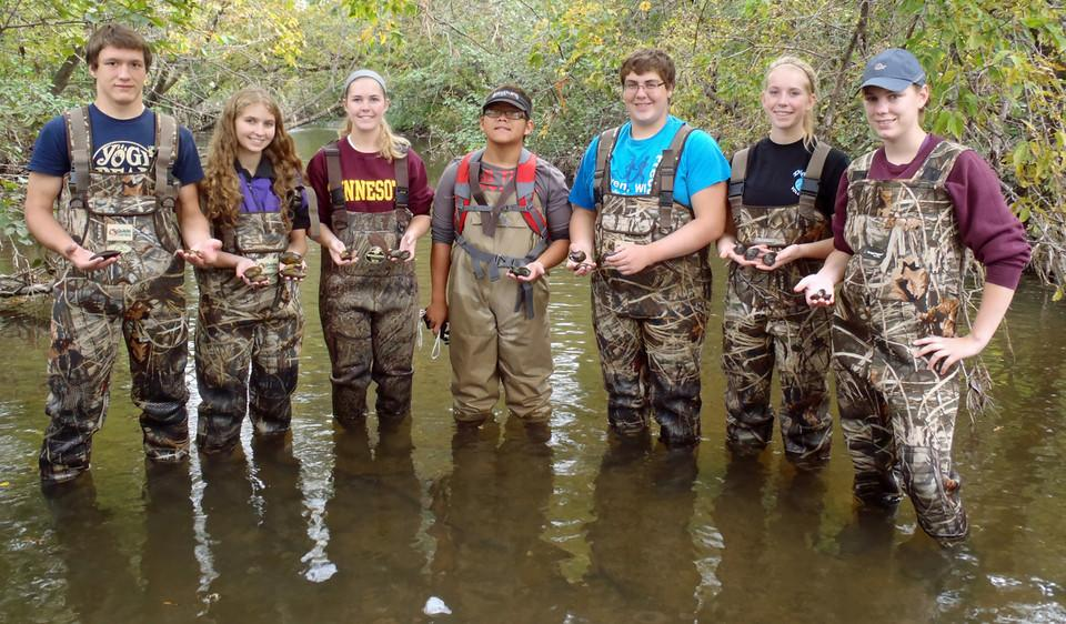 Seven students in waders holding fishing supplies