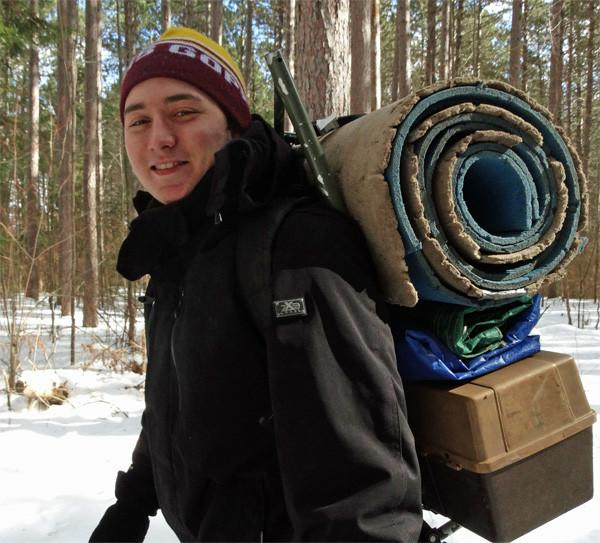 A student outside in the winter with a lot of supplies carried on his back